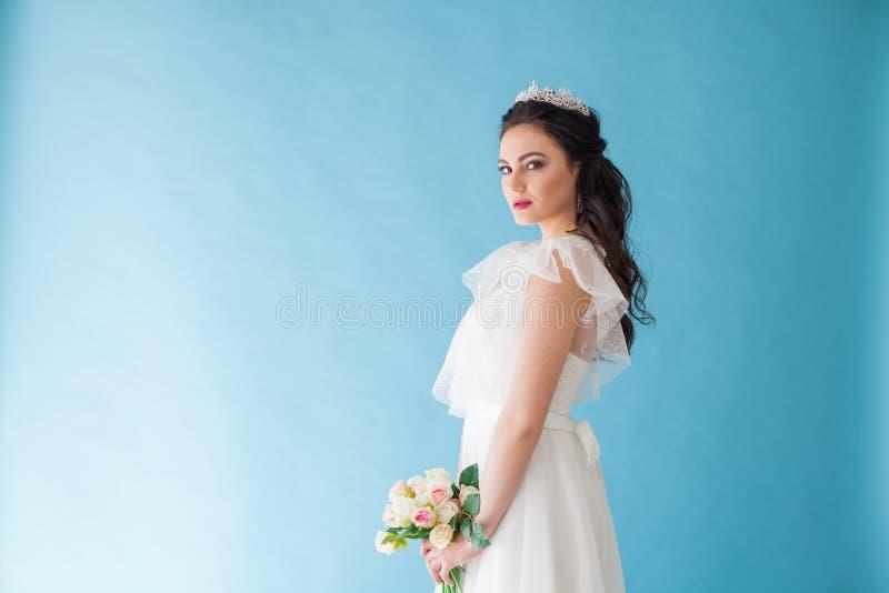 Princesa Bride em um vestido branco com uma coroa em um fundo azul foto de stock