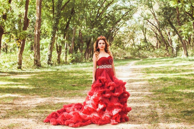 Princesa com a coroa no vestido vermelho nebuloso fotografia de stock royalty free