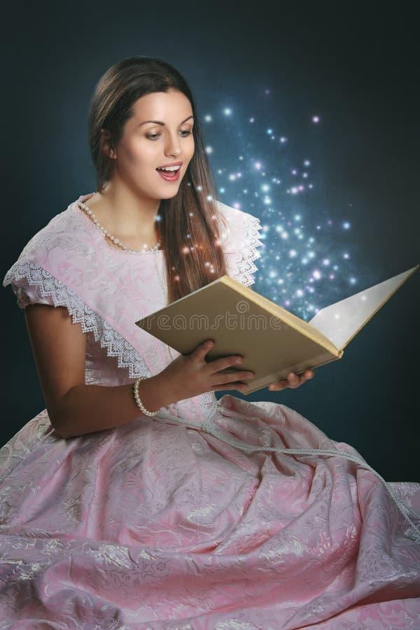 Princesa del cuento de hadas con el libro mágico imagen de archivo