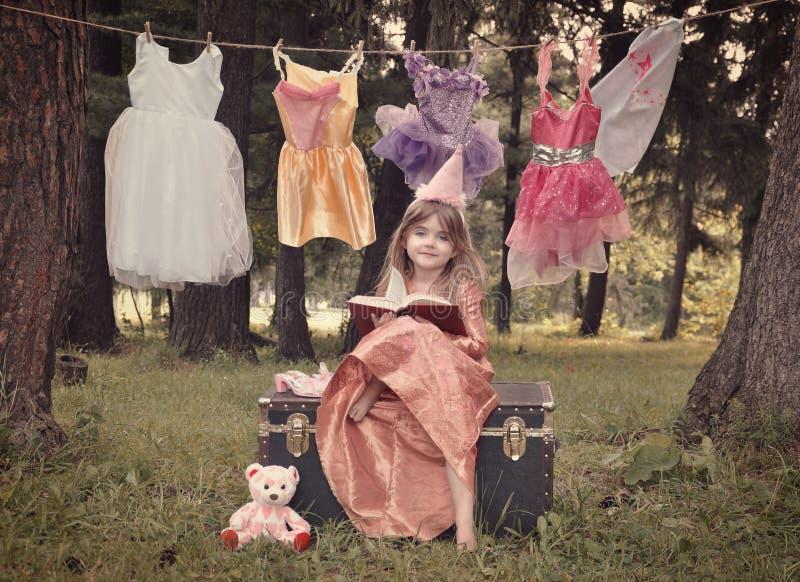 Princesa do conto de fadas nas madeiras que lê o livro da história fotos de stock