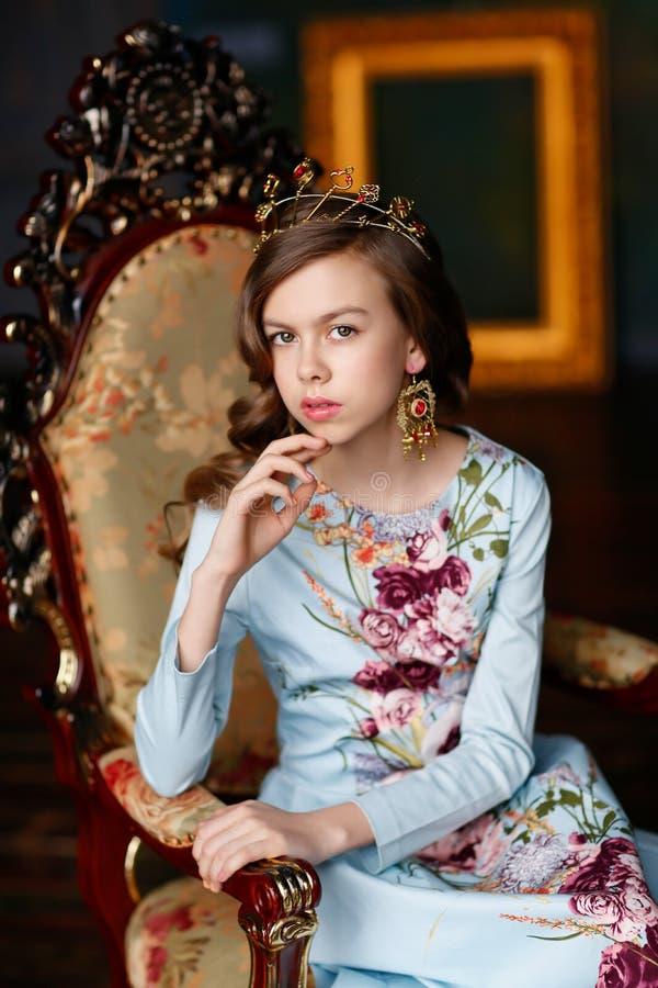 Princesa elegante en vestido azul con el pelo ondulado y una corona en ella imagen de archivo