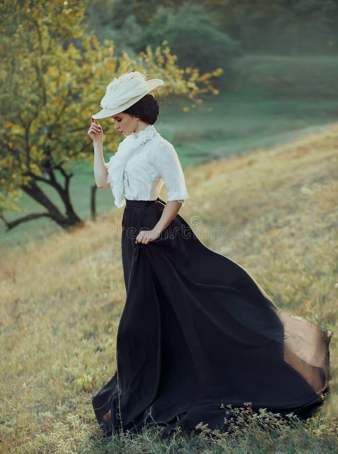 A princesa em um vestido e em vestir do vintage um chapéu branco com penas que anda ao longo das inclinações dos montes O vento imagens de stock