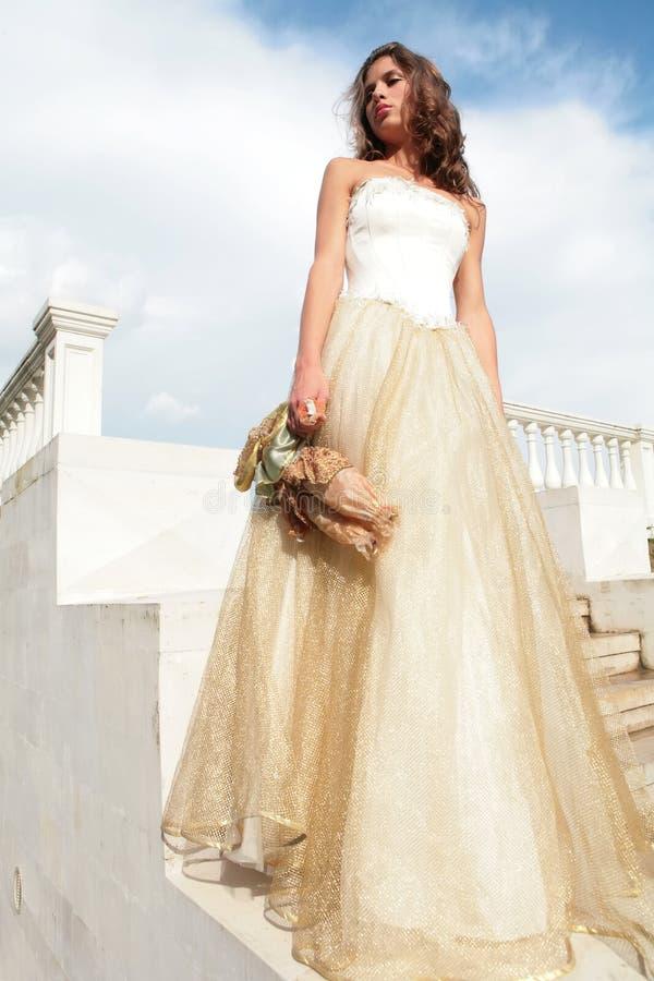 Princesa no vestido dourado com brinquedo amado fotografia de stock