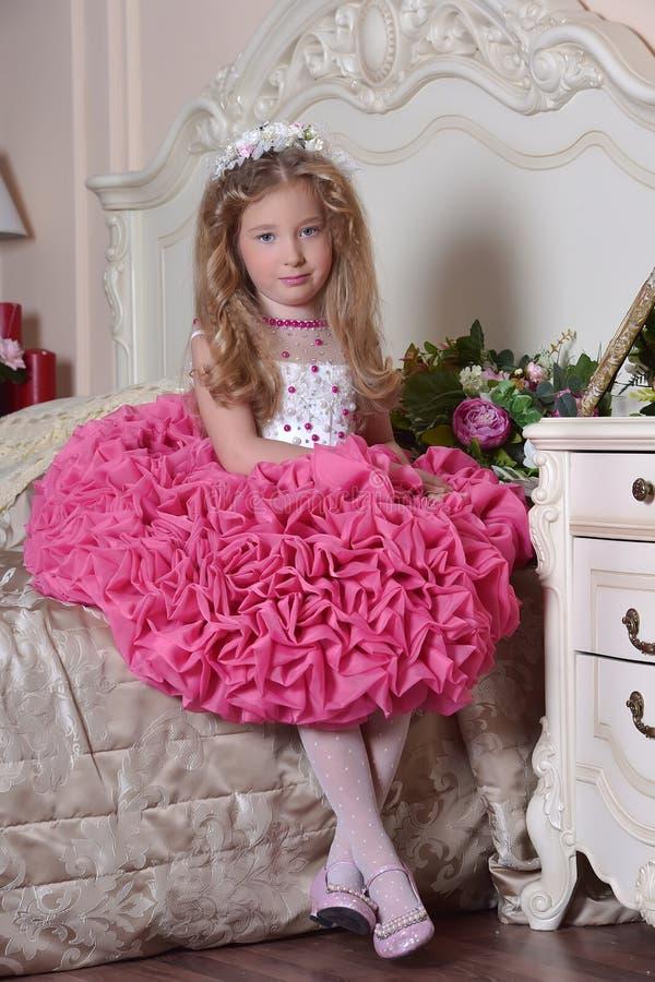 Princesa nova em um assento cor-de-rosa elegante do vestido imagens de stock royalty free