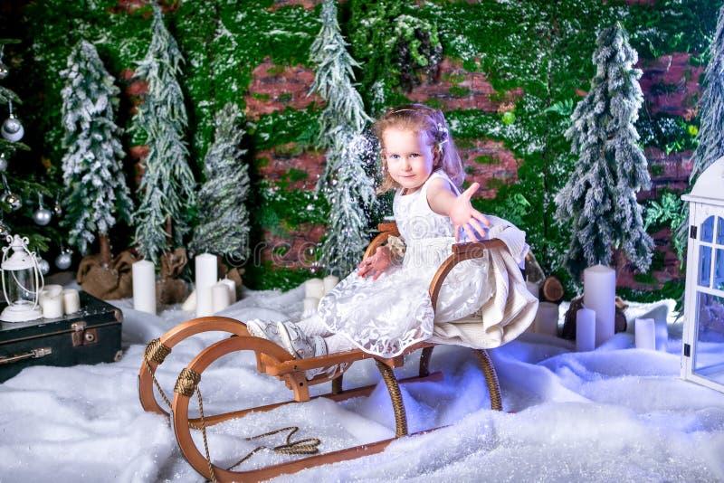 A princesa pequena bonito em um vestido branco está sentando-se em um trenó e em uma neve de jogo foto de stock