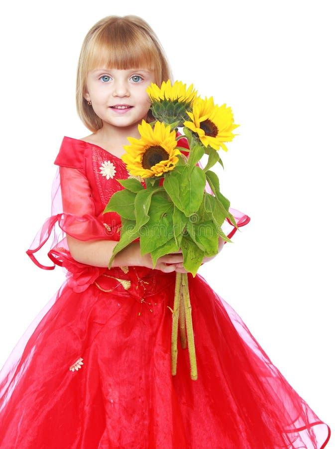 Princesa pequena guardando flores amarelas brilhantes fotografia de stock royalty free