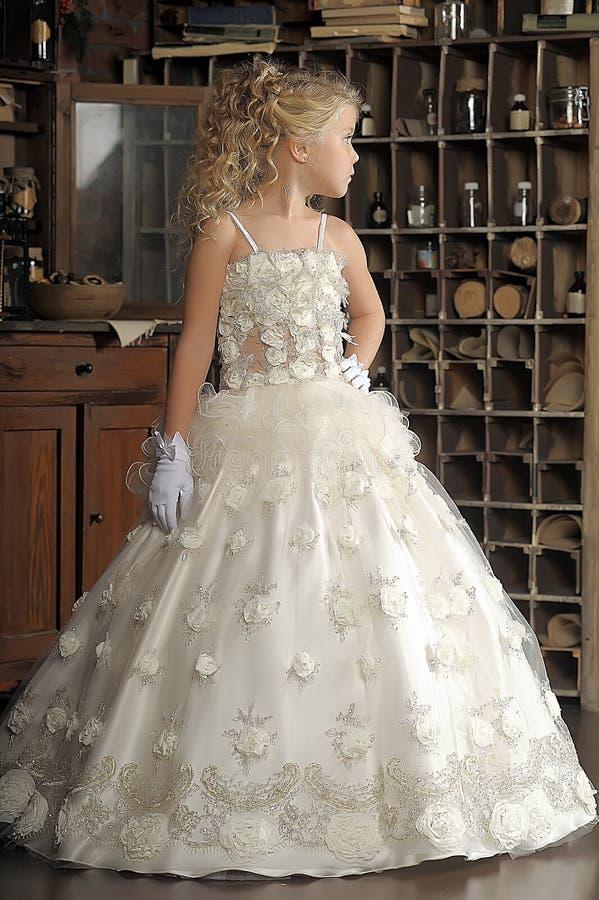 Princesa pequena no vestido branco e em flores vermelhas fotos de stock royalty free