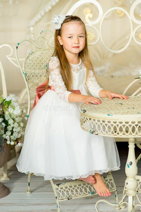 Princesa pequena que senta-se perto da tabela fotos de stock royalty free