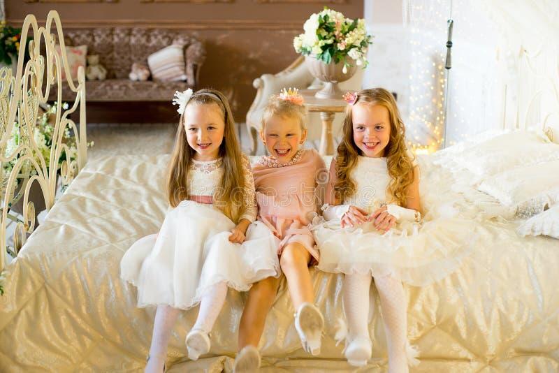 Princesa três pequena que senta-se na cama imagem de stock