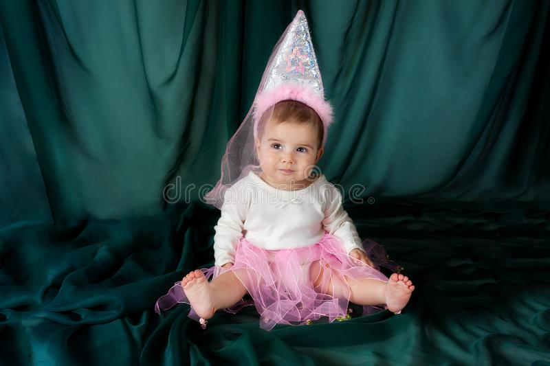 Princess Baby With Tall Sparkly Hat and Veil on Green Backdrop w royalty free stock image