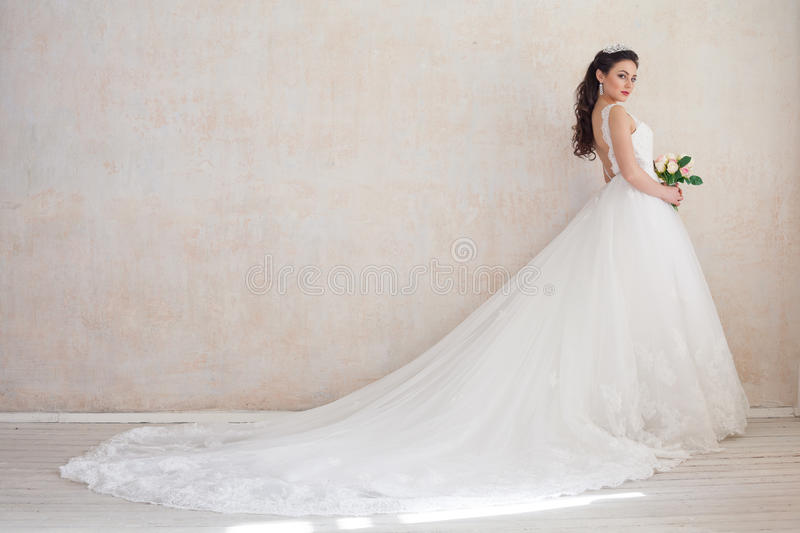 Princess Bride in a wedding dress standing in a room of vintage. Princess Bride in a wedding dress with a train standing in a room of vintage royalty free stock photo