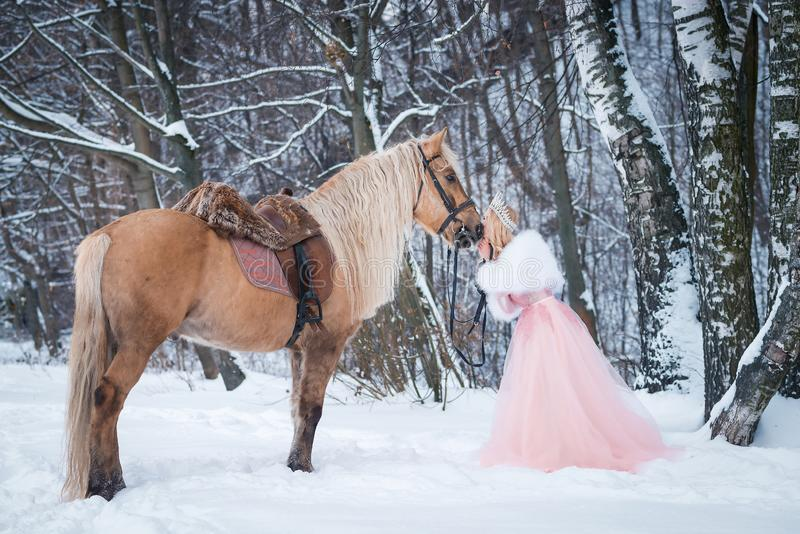 Princess in crown with horse in winter. Fairy tale. Romantic fanatsy royalty free stock photos