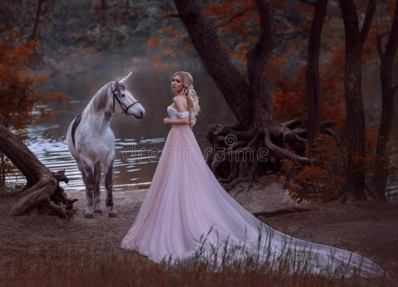 The princess met a unicorn in the forest. The blonde girl with a gentle make-up, is dressed in a long vintage dress with. A lush skirt and train. Artistic royalty free stock image