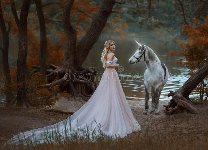 The princess met a unicorn in the forest. The blonde girl with a gentle make-up, is dressed in a long vintage dress with royalty free stock image