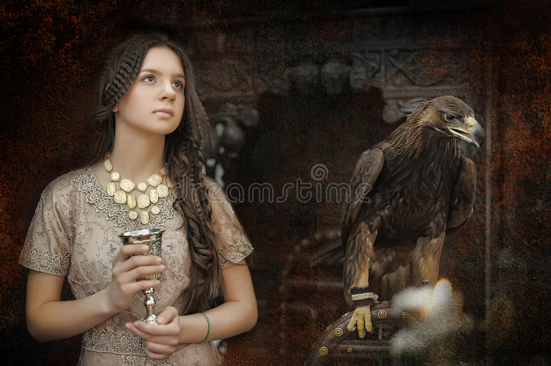 Princess next to the eagle with the cup in her hands. Princess next to the throne with an eagle stock photography