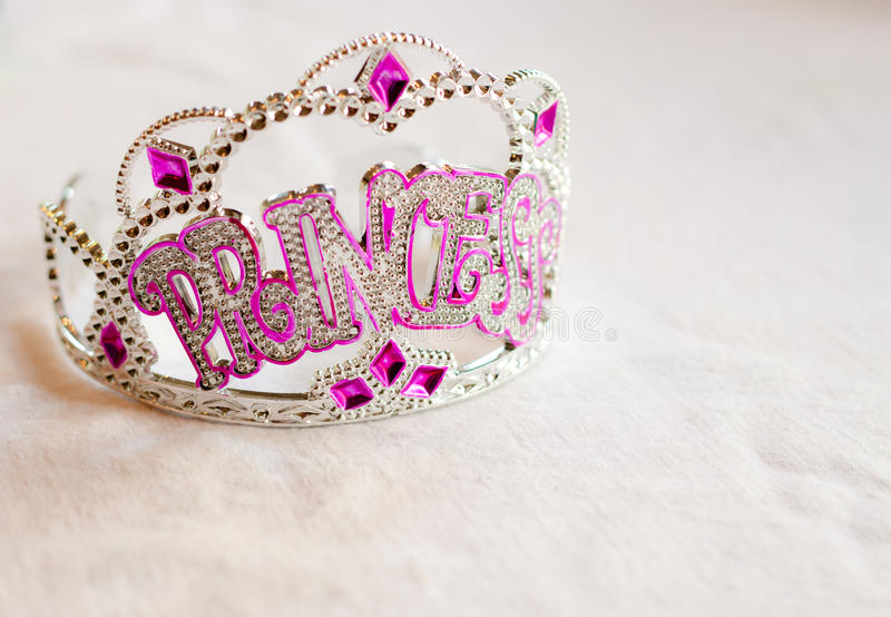 Princess party tiara. A sparkly rhinestone tiara with silver and purple beads that spells out Princess sits on a white tablecloth royalty free stock photography