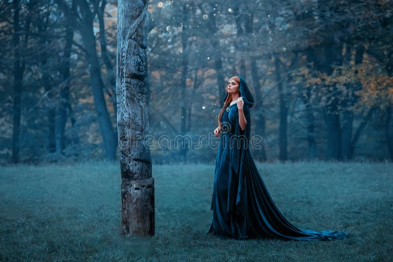 Princess with red long hair dressed in blue expensive velvet royal cloak-dress, girl got lost in dark foggy forest, art stock images