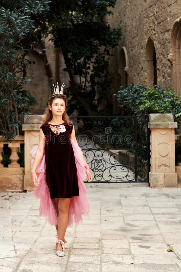 The princess in a red velvet dress and pointe shoes dances in an ancient castle near the garden behind the forged fence royalty free stock photos
