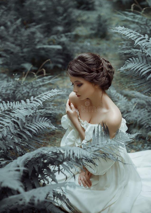 Princess siedzi na ziemi w lesie wśród mech i paproci, Na damie jest biała rocznik suknia z głębokim obraz royalty free