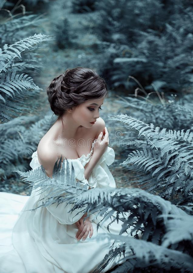 The princess sits on the ground in the forest, among the fern and moss. An unusual face. On the lady is a white vintage stock image