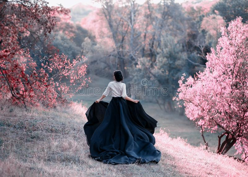 Princess in a vintage dress escapes. Walk through the picturesque autumn hills at sunset in pink tones. A long train of royalty free stock images