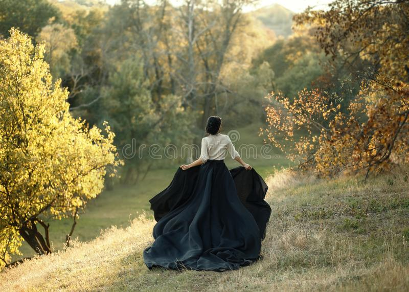 Princess in a vintage dress. Walk along the picturesque autumn hills at sunset. A long train of black skirt fluttered on the run. Photo of a brunette girl with royalty free stock photo