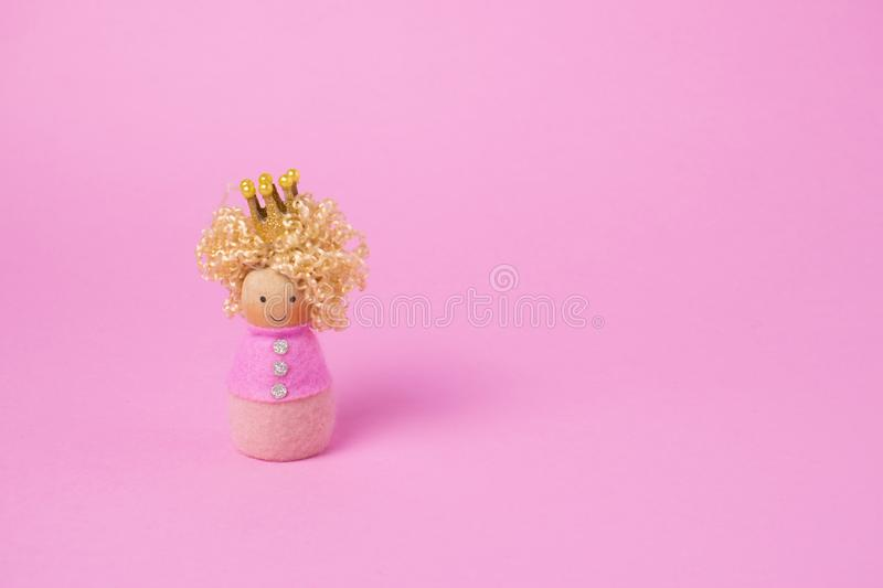 Princess wooden doll on pink background. minimal concept. copy space stock photography