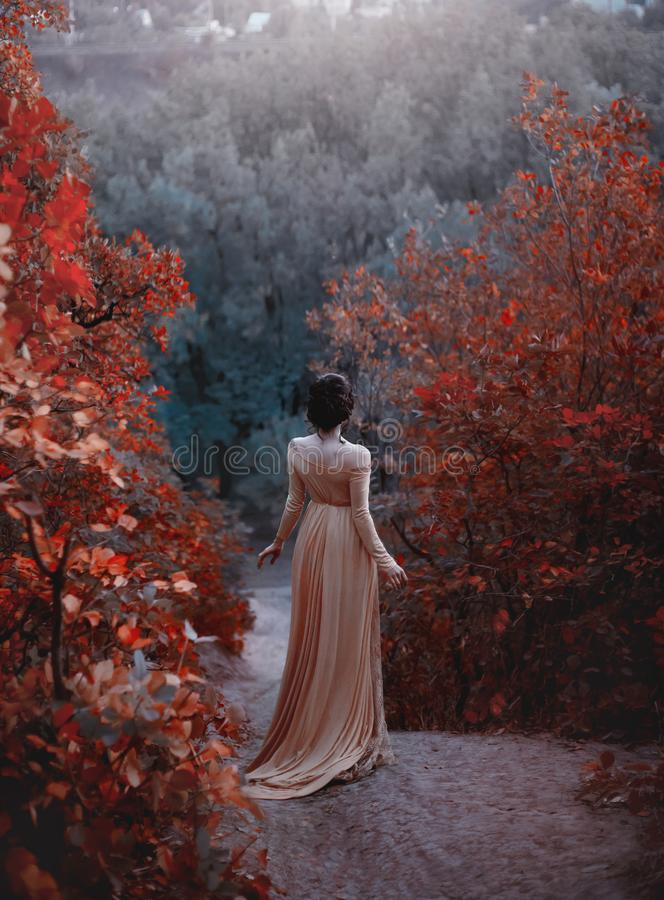 The princess in a yellow vintage dress in the Renaissance is walking along the picturesque autumn hills at dusk. Photo stock photos