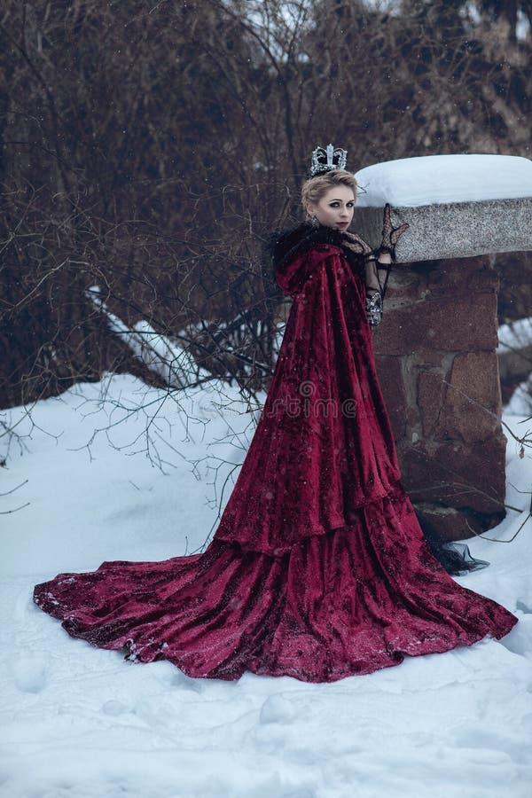 Princesse dans un manteau rouge dans la neige photos libres de droits
