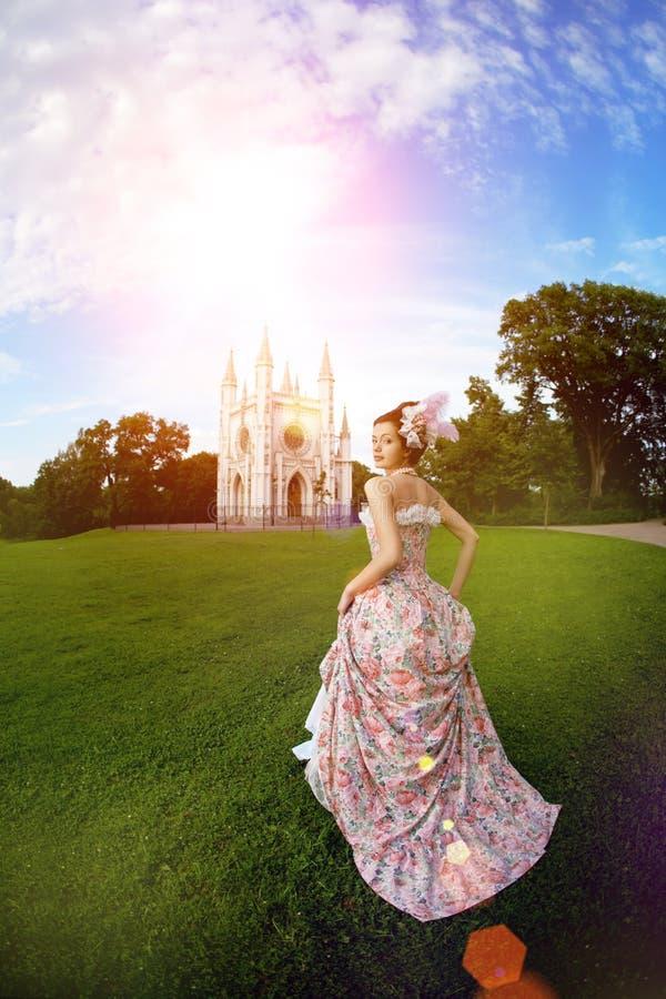 Princesse dans une robe de vintage avant le château magique photo stock