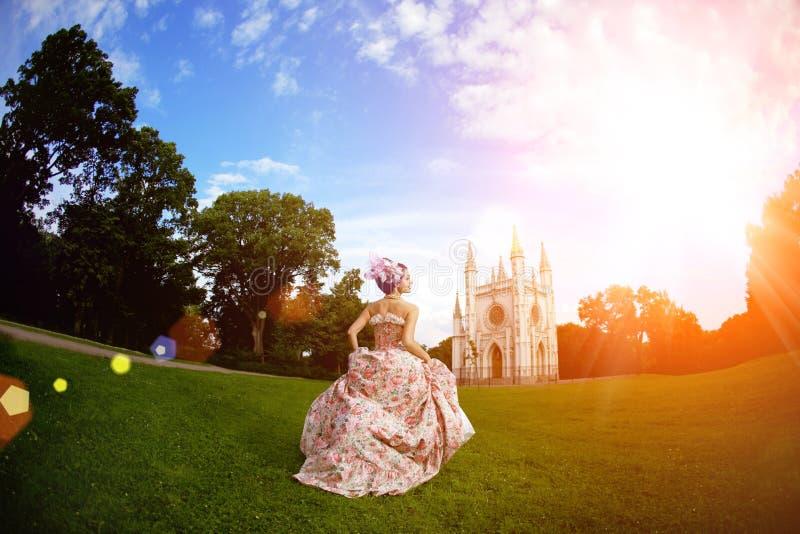 Princesse dans une robe de vintage avant le château magique images stock