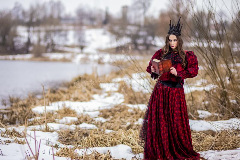 Princesse féerique mystérieuse dans la robe rouge et la couronne noire lisant le vieux livre Pose en Forest Outdoors images libres de droits