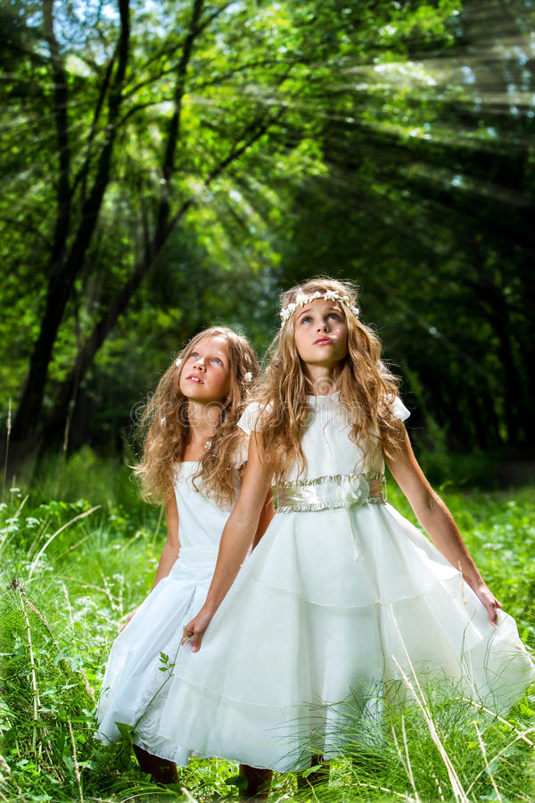 Princesses de Litte portant des robes de blanc en bois. images stock