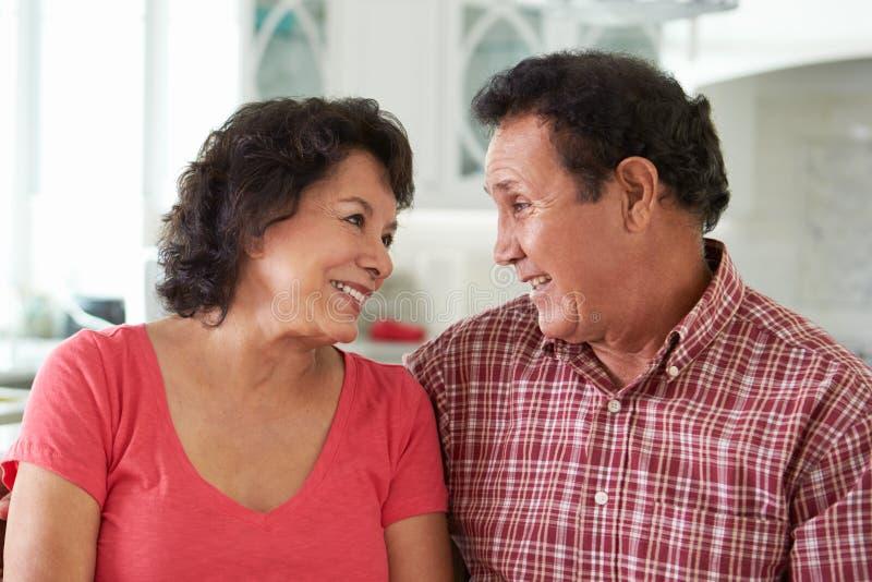 Principal et épaules tirés des couples hispaniques supérieurs à la maison photo stock