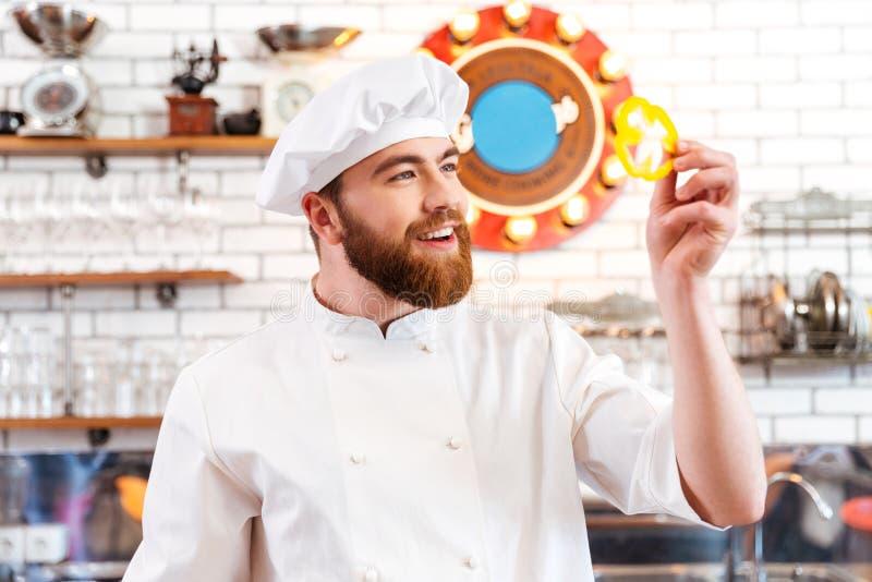 Principal rebanada que se sostiene sonriente del cocinero de paprika amarillo imagen de archivo
