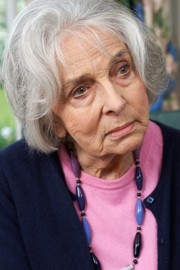 Principal y hombros tirados de mujer mayor pensativa en casa fotos de archivo