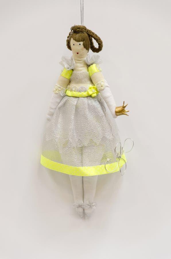 Principessa grassottella della bambola fatta a mano con una corona nella h fotografia stock