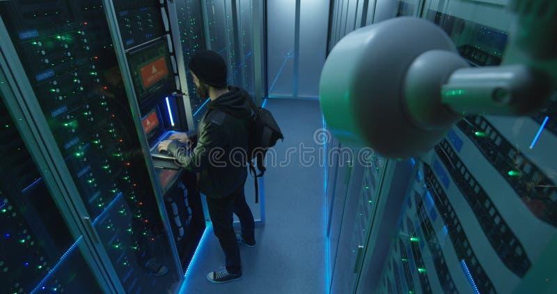 Principio del pirata informático a cortar mientras que comprueba la cámara de seguridad foto de archivo
