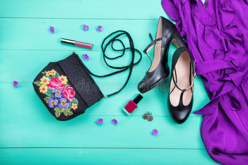 Pring clothes, women`s clothes. Spring clothes, women`s clothes - a purple dress, embroidered bag, black heels, earrings, nail polish, lipstick. turquoise wooden stock photo