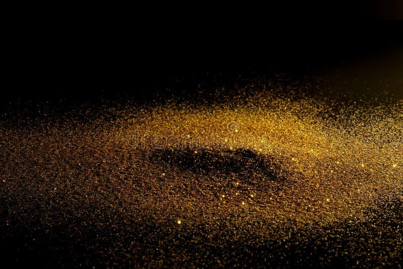 Prinkle-Funkeln-Goldstaub auf einem schwarzen Hintergrund stockbilder