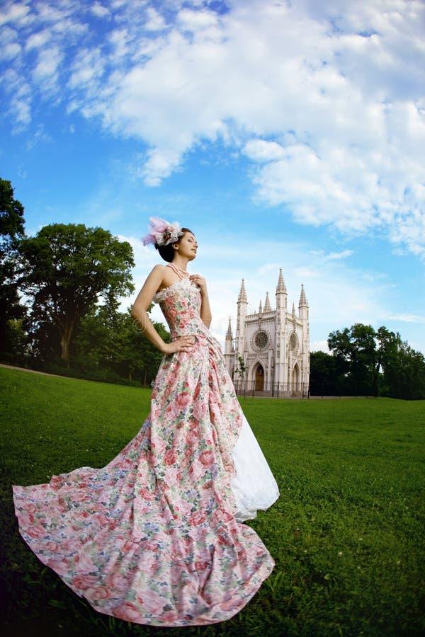 Prinses in een uitstekende kleding vóór kasteel stock fotografie