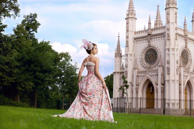 Prinses in een uitstekende kleding vóór kasteel stock foto