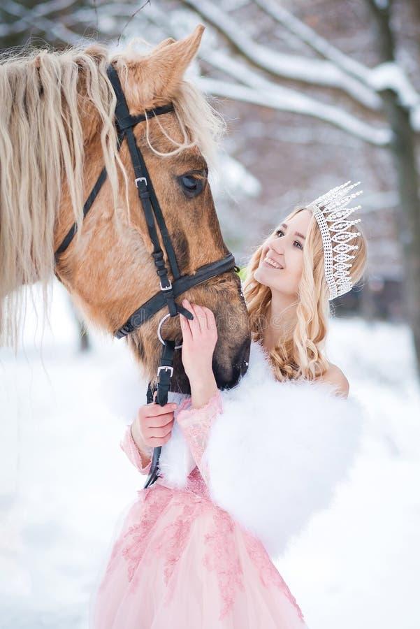 Prinses in kroon met paard in de winter Abstracte fantasieachtergronden met magisch boek Romantische fanatsy stock foto