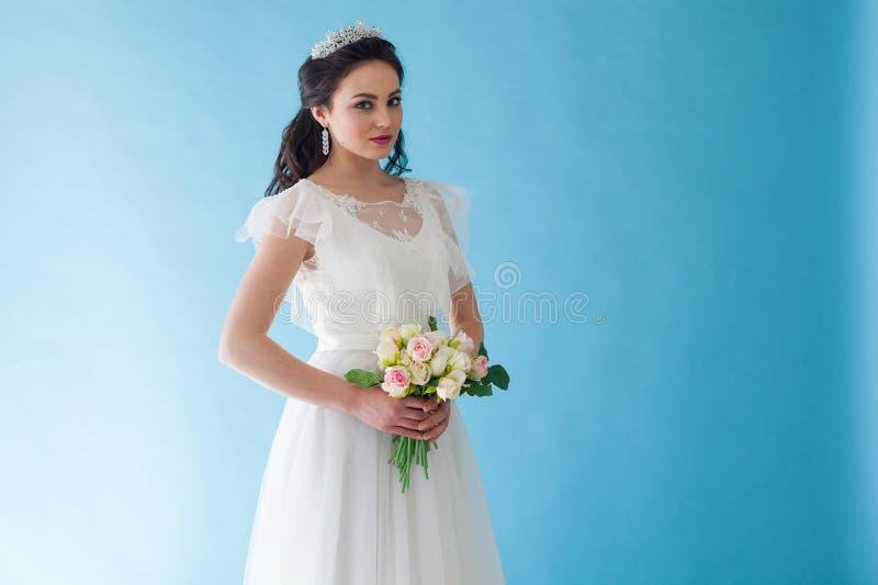 Prinsessa Bride i en vit klänning med en krona på en blå bakgrund royaltyfri bild