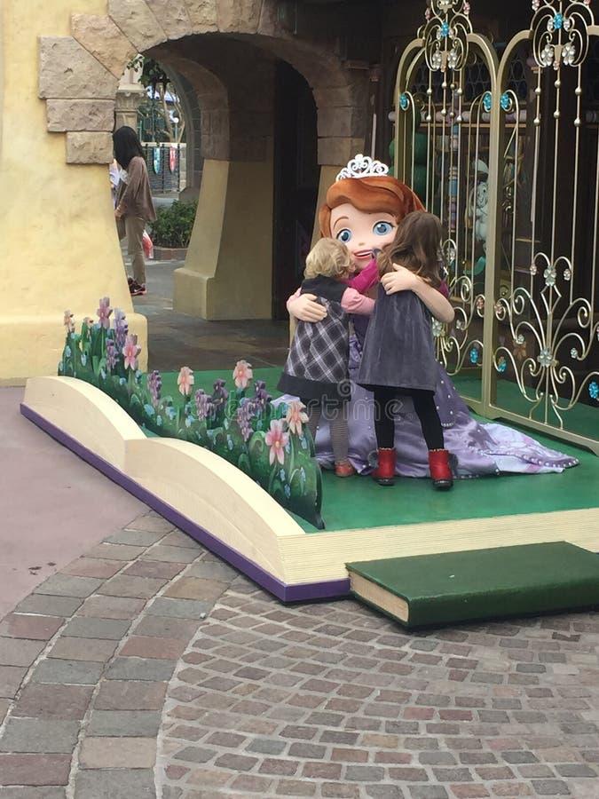 Prinsessa som kramar små flickor på Disney World, Hong Kong arkivfoton