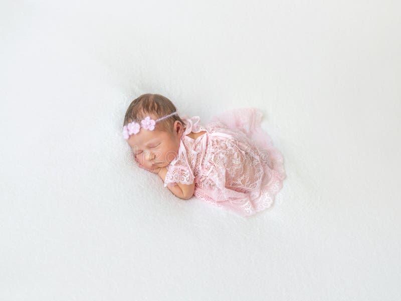 Prinsessan behandla som ett barn att ta sig en tupplur i snörd åt rosa färgdräkt royaltyfri fotografi