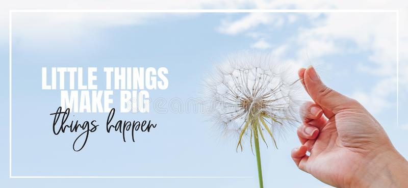 Little things make big things happen. Hand holding Dandelion flower pointing to blue sky, close up photography. Banner design, poster design. Positive royalty free stock photos