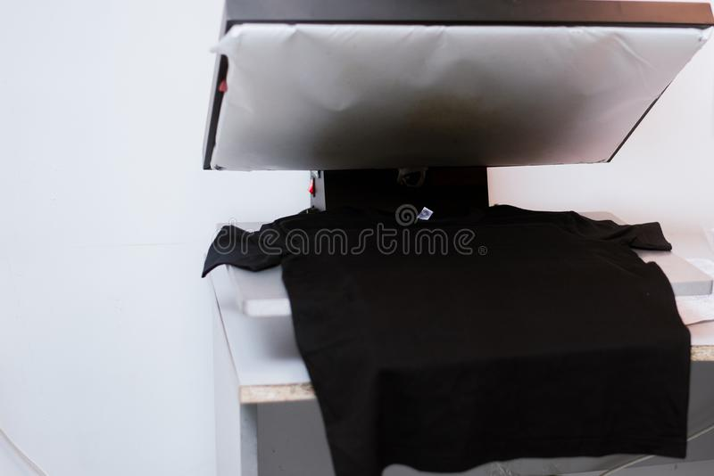 Big press to translate images on the fabric. Print on black t-shirt. Big press to translate images on the fabric stock photography