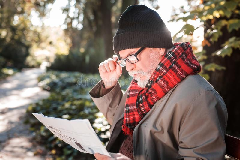 Smart aged man reading a morning newspaper royalty free stock photos