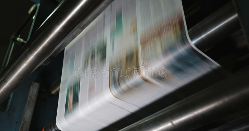 Print plant factory. Newspaper printing at a plant. Newspaper printed on a printing house machine. Close up stock images